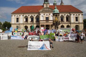 Bündnismitglieder mit Bannern vor dem Rathaus