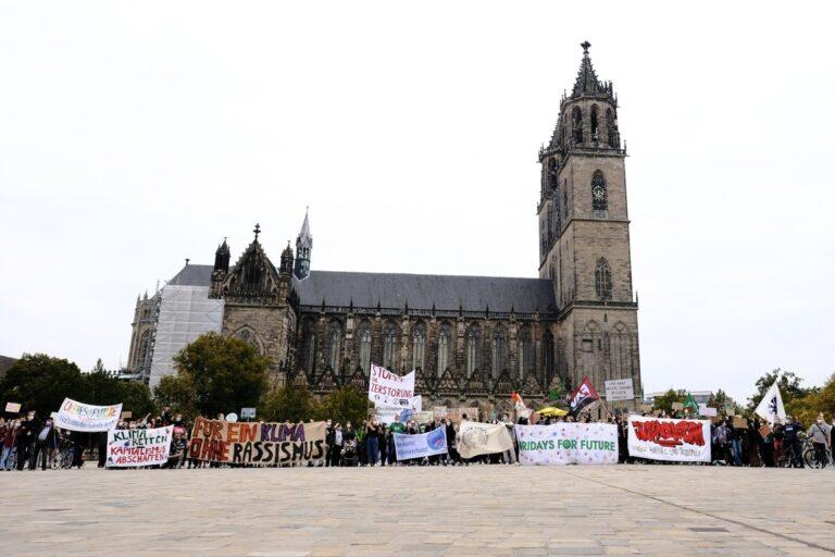 Gruppenfoto vor dem Dom mit vielen Bannern am Ende der Laufdemo